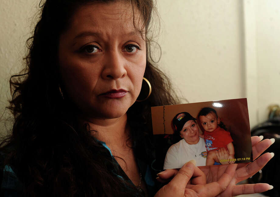 Virginia Ortiz holds a photo of herself with grandson Pedro Antonio Salgado Jr., who died after being left alone in a bathtub last year. Photo: BILLY CALZADA/gcalzada@express-news.net