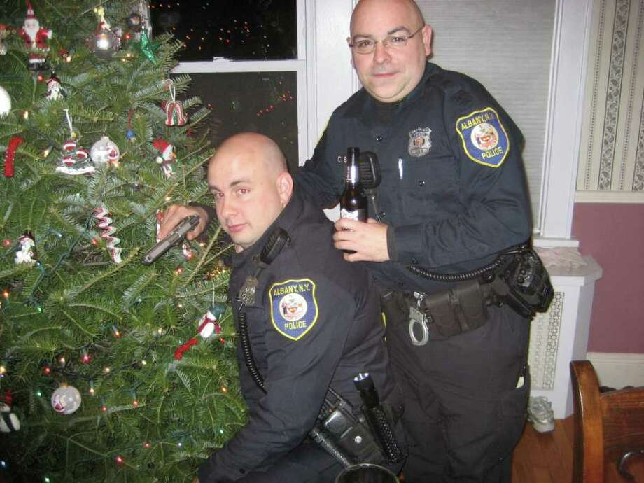 Albany police officers Sean Slingerland, left, and Charles Batchelor are shown at Officer Robert E. Schunk II's home. The department is investigating