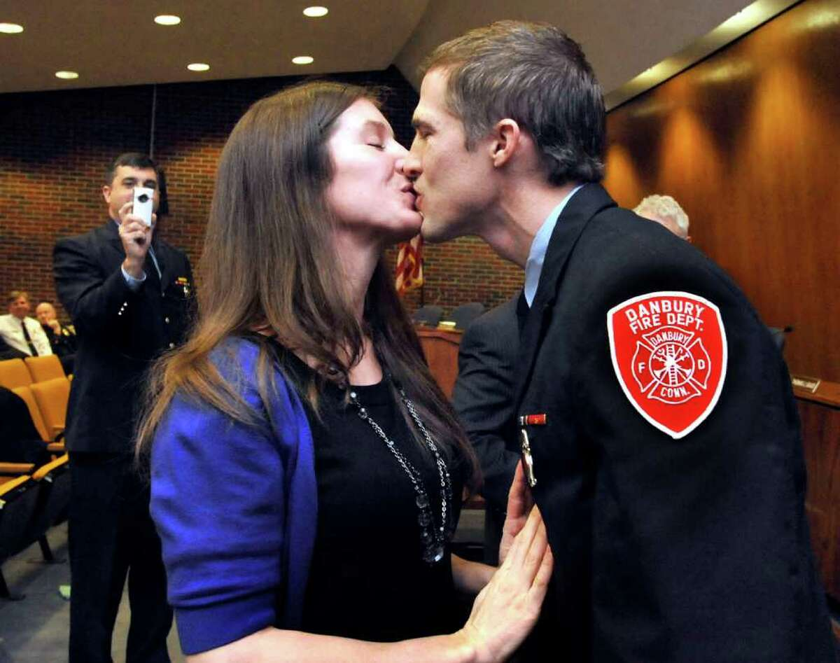 John Halas, of the Danbury Fire Department, gets a congratulatory kiss from his girlfriend, Aly Meeker, after she pinned the badge of lieutenant on him during a ceremony in Danbury's City Hall, Monday, Feb. 7, 2011.