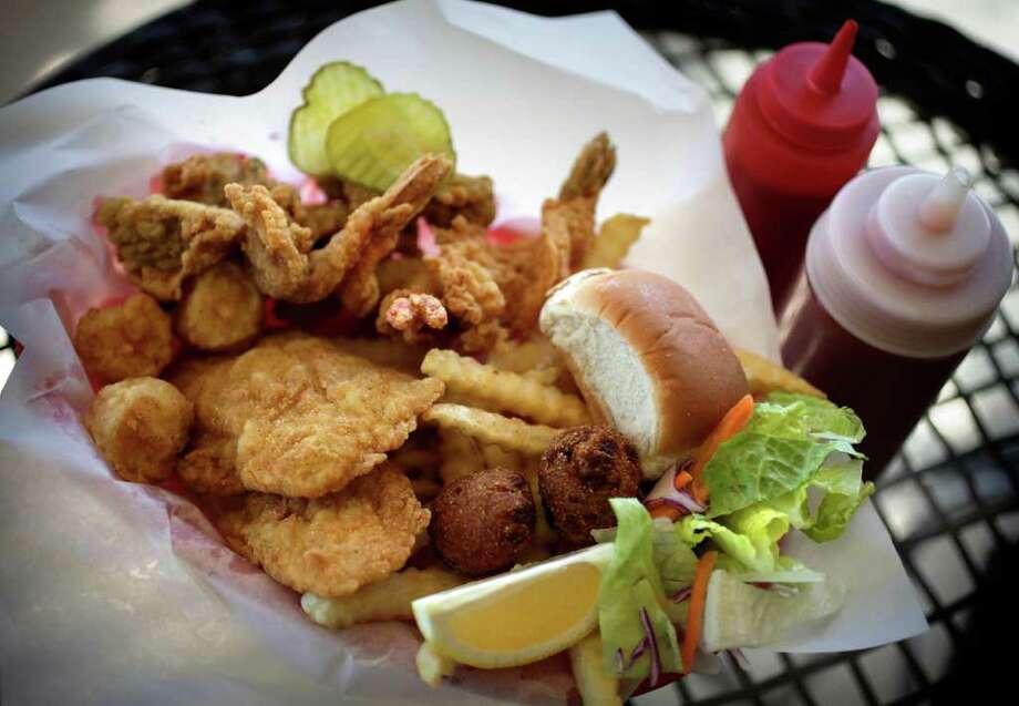 The Seaman's Platter at Fishland Fish Market combines shrimp, scallops, oysters, fish, fries, a roll and salad. Photo: BOB OWEN, SAN ANTONIO EXPRESS-NEWS / SAN ANTONIO EXPRESS-NEWS