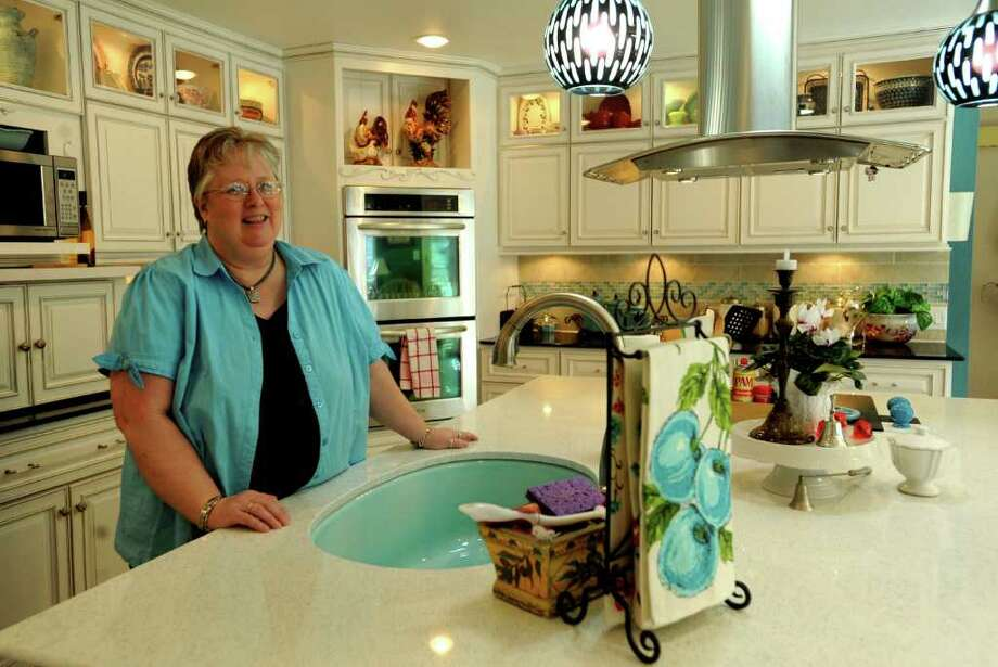"Jo Carlton describes her kitchen as ""sort of a California modern with a touch of vintage."" The color turquoise predominates the palette with a few pops of red. Photo: BILLY CALZADA, SAN ANTONIO EXPRESS-NEWS / gcalzada@express-news.net"