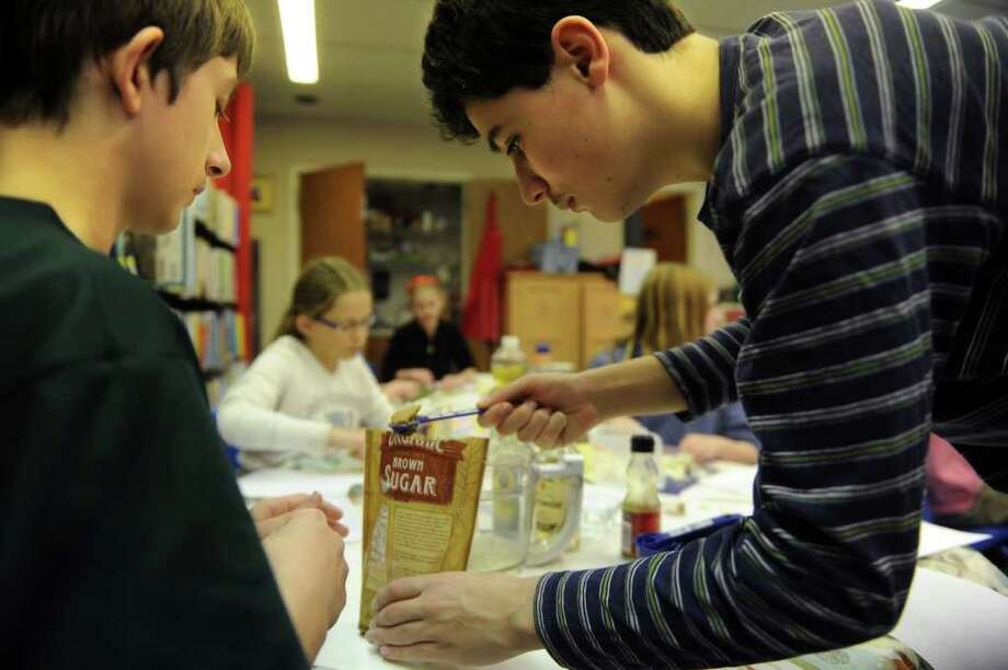 Tony Abbazia, 14, right, and Brendon Watcke, 13, left, measure brown sugar during the Pequot Library's Wonton Winter Wonderland Event in honor of the Chinese New Year on Friday, February 4, 2011. Photo: Lindsay Niegelberg / Connecticut Post