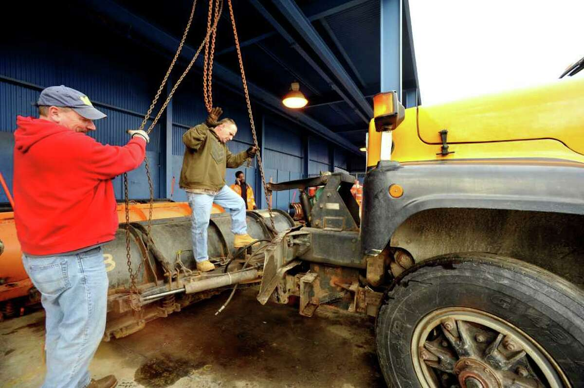 Ed Archer, left, and Chris McGran, of the Danbury Public Works Department, attach plows to town trucks in preperation for the next snow, Monday, Feb. 7, 2011.