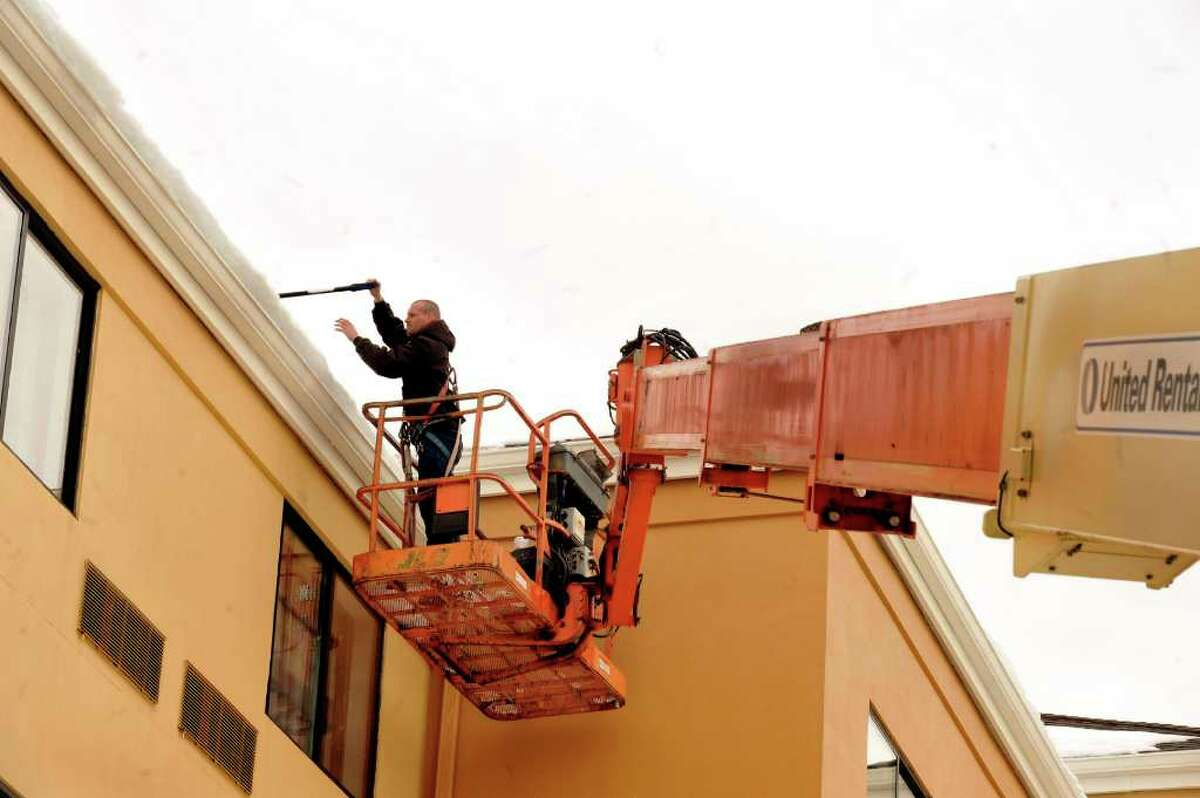 Dan Brahier, chief engineer, uses an ultra boom to clear snow from the roof of Courtyard by Marriott in Danbury, Feb. 7, 2011.