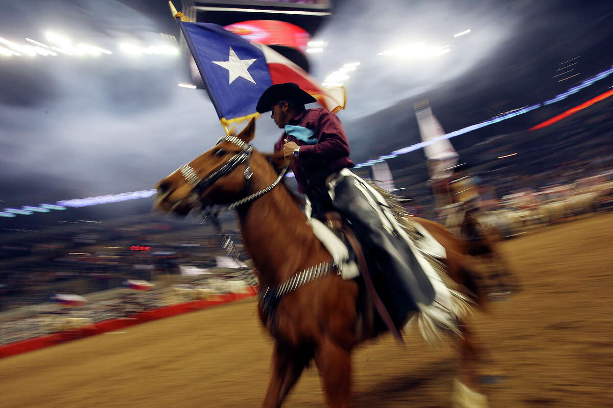 A member of the Palomino Patrol Drill Team carries a Texas flag during the Grand Entry Monday Feb. 7, 2011 during the San Antonio Stock Show & Rodeo at the AT&T Center.