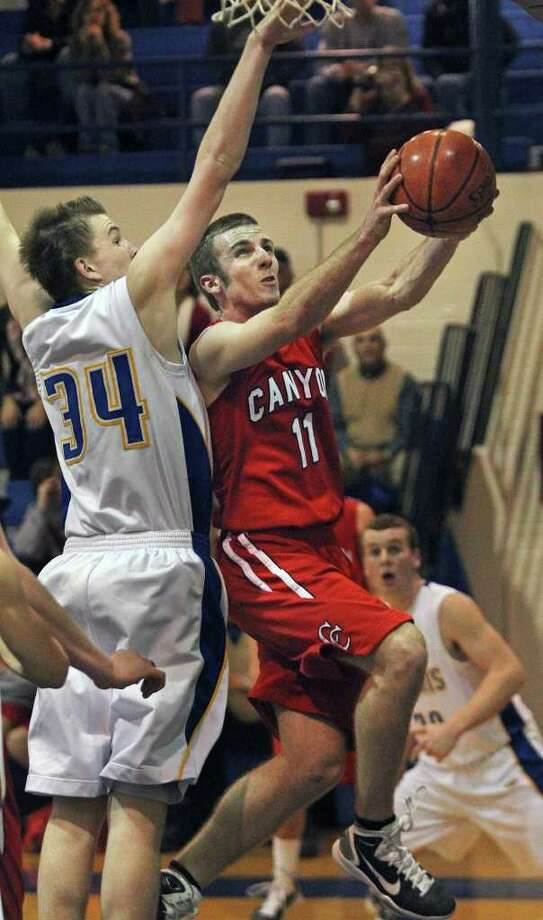 Canyon's Cody Karrer goes to the hoop against Alamo Heights' Shelby Lane in the Mules' 58-47 win last week. Photo: TOM REEL, SAN ANTONIO EXPRESS-NEWS / © 2010 San Antonio Express-News