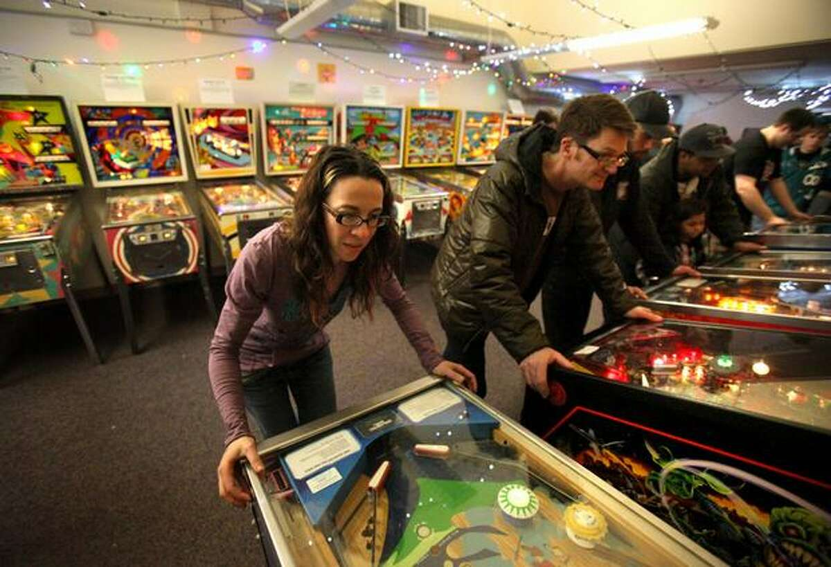 Wendy Woldenberg, left, and Bob Anderton, right, play pinball machines while celebrating the 20th anniversary of their first date on Saturday, February 5, 2011 at the Seattle Pinball Museum in Seattle's International District. The museum was part of the Storefronts project and was so successful that the owners are hoping to continue the new business. Storefronts is a project to fill vacant spaces in Pioneer Square and the International District with art, activity and vibrancy. See photo gallery.