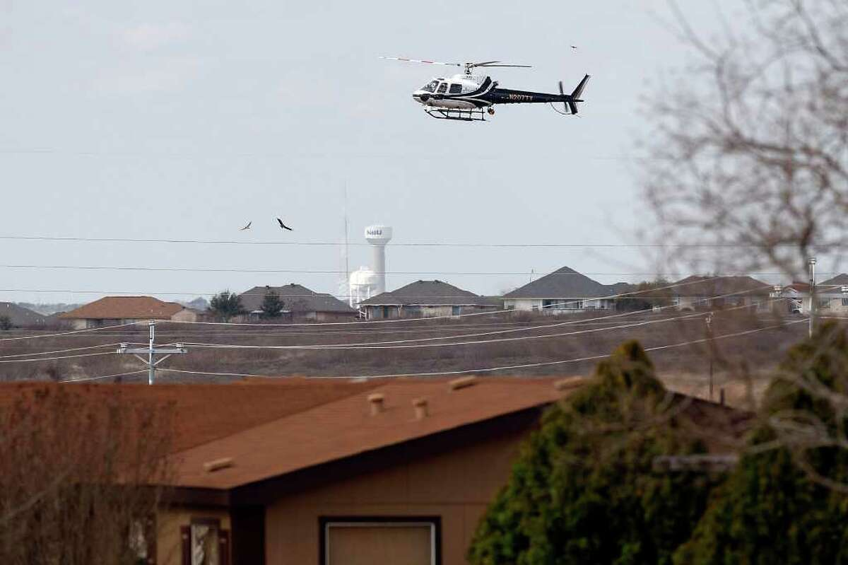 A Department of Public Safety helicopter flies over the neighborhood of missing 18-month-old Joshua Davis, Jr. in New Braunfels as investigators work the backyard on Feb. 18.