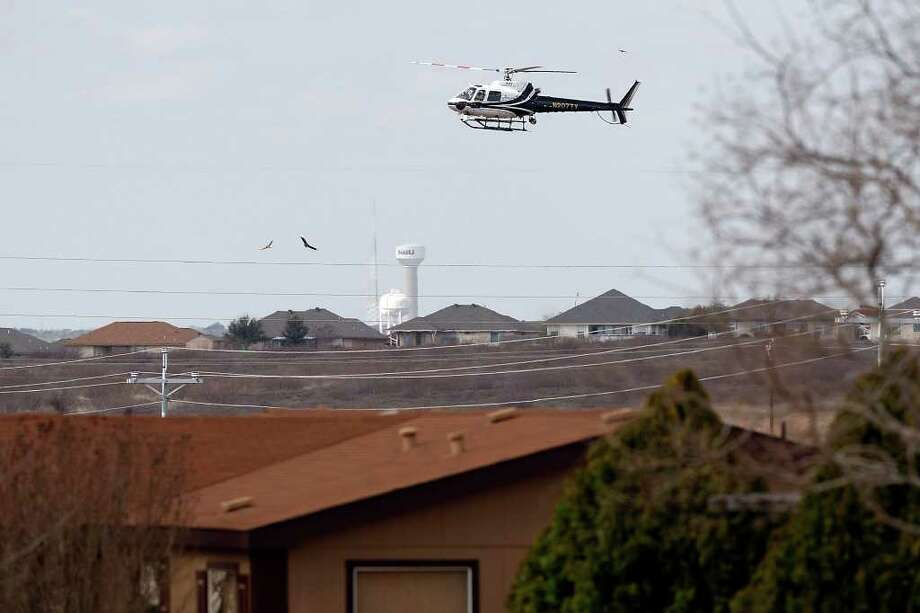 A Department of Public Safety helicopter flies over the neighborhood of   missing 18-month-old Joshua Davis, Jr. in New Braunfels as investigators work the backyard on Feb. 18. Photo: JERRY LARA, San Antonio Express-News / glara@express-news.net