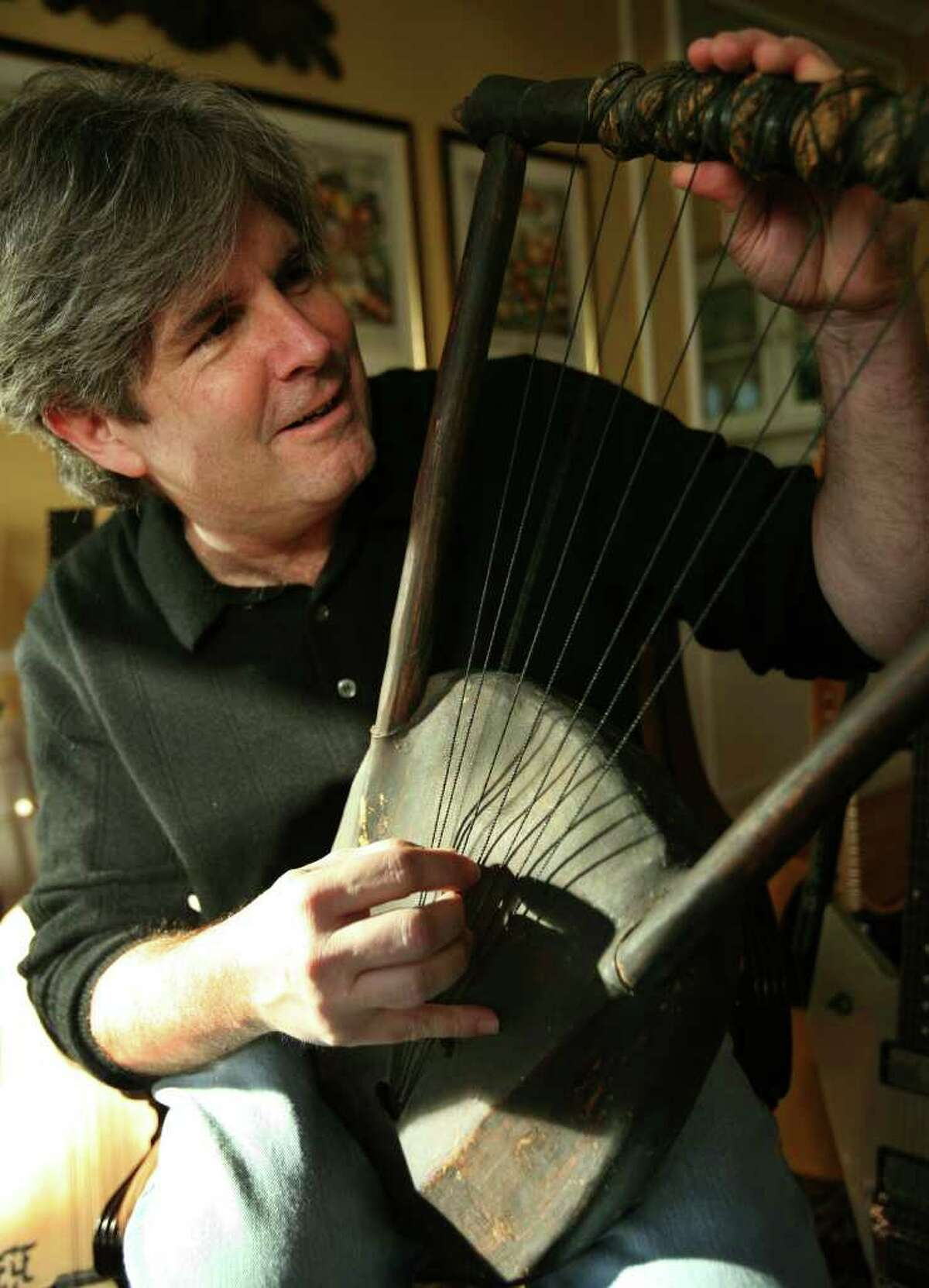 Harvey Newquist of Fairfield, demonstrates an African stringed instrument called a nyatiti. Plucked tones can be raised and lowered by turning the wheels at the top of the instrument.