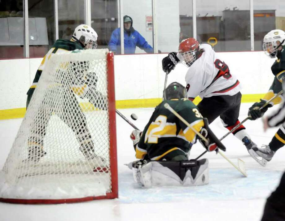 Alex Liebers, # 9, of Greenwich High School, center, attempts a shot that is blocked by Trinity Catholic goalie, Ben Fumega, # 32, during first period action of the Greenwich High School vs. Trinity Catholic High School boys hockey game, at Dorothy Hamill Rink, Byram, Tuesday afternoon, Feb. 8, 2011 Photo: Bob Luckey / Greenwich Time