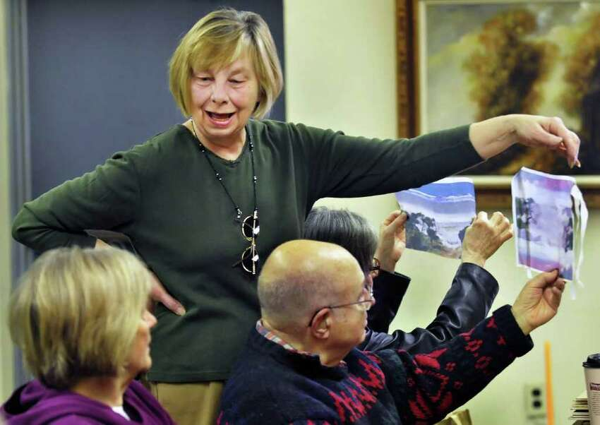 Luba Rickett, standing, of Colonie shows examples of her encaustic process silk photo prints during the senior photography club weekly meeting at the Louise Corning Senior Center in Albany on Feb. 4. Several programs are run out the of the building, the largest senior center in the city of Albany. The agency and the services must leave the building so the city can sell it to ease a budget gap. There are also structural problems in part of the building. (John Carl D'Annibale / Times Union)
