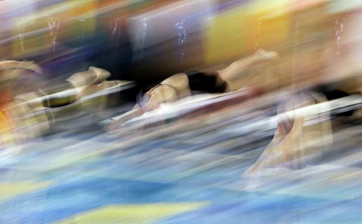 Swimmers dive into the pool to start their race in the Region VII-4A swim meet at Josh Davis Natatorium on Tuesday, Feb. 8, 2011. Kin Man Hui/kmhui@express-news.net