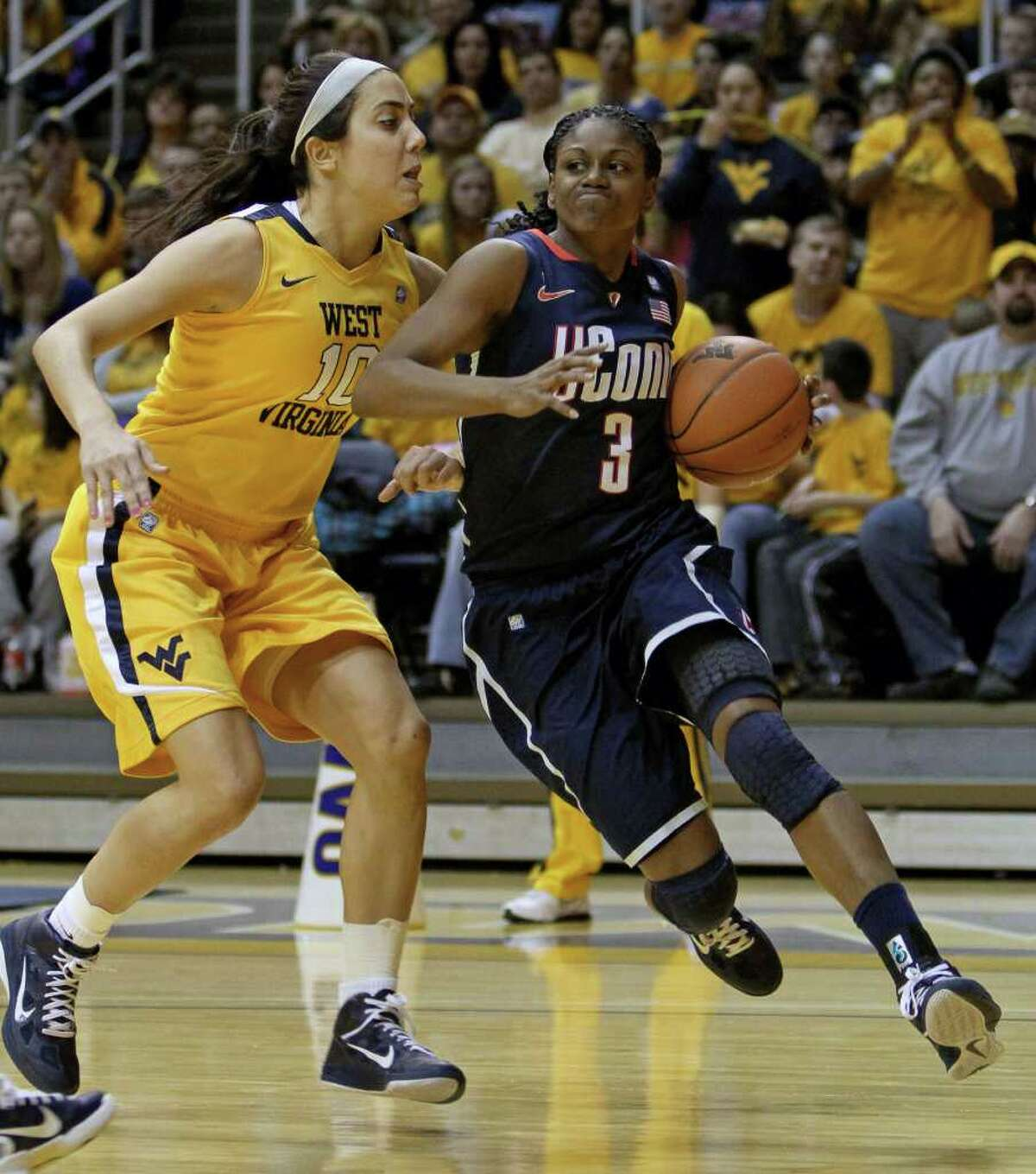 Connecticut's Tiffany Hayes (3) drives by West Virginia's Liz Repella (10) in the first half of an NCAA college basketball game in Morgantown, W.Va. on Tuesday, Feb. 8, 2011. (AP Photo/David Smith)