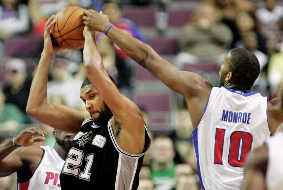 San Antonio Spurs' Tim Duncan (21) is fouled by Detroit Pistons' Greg Monroe after grabbing a rebound in the first half of an NBA basketball game, Tuesday, Feb. 8, 2011, in Auburn Hills, Mich. Photo: AP