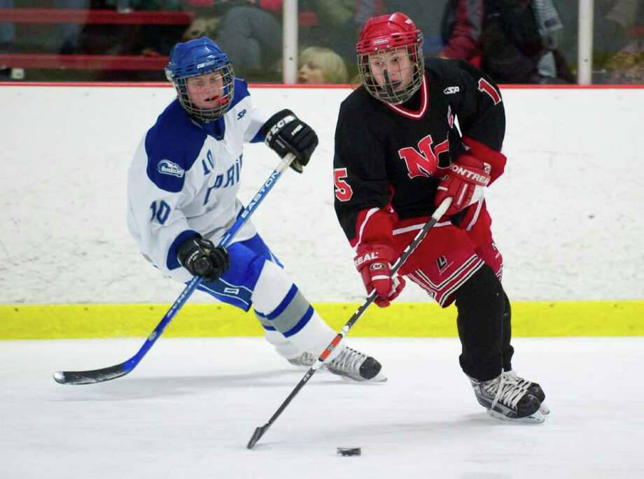 Darien's Ellie Bullitt, left, and New Canaan's Jana Persky, right, during a girls hockey game in Darien, Conn. on Wednesday, Jan. 20, 2010. Photo: Chris Preovolos / Stamford Advocate