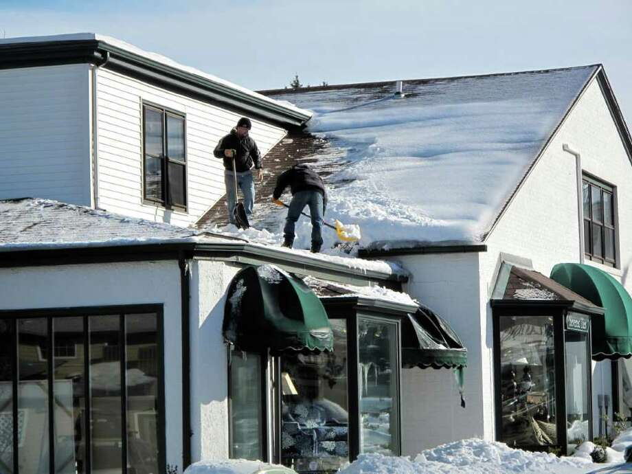 Clearing snow off the roof on Cherry Street. Photo: Contributed Photo;Paresh Jha Staff Photo, Contributed Photo / New Canaan News