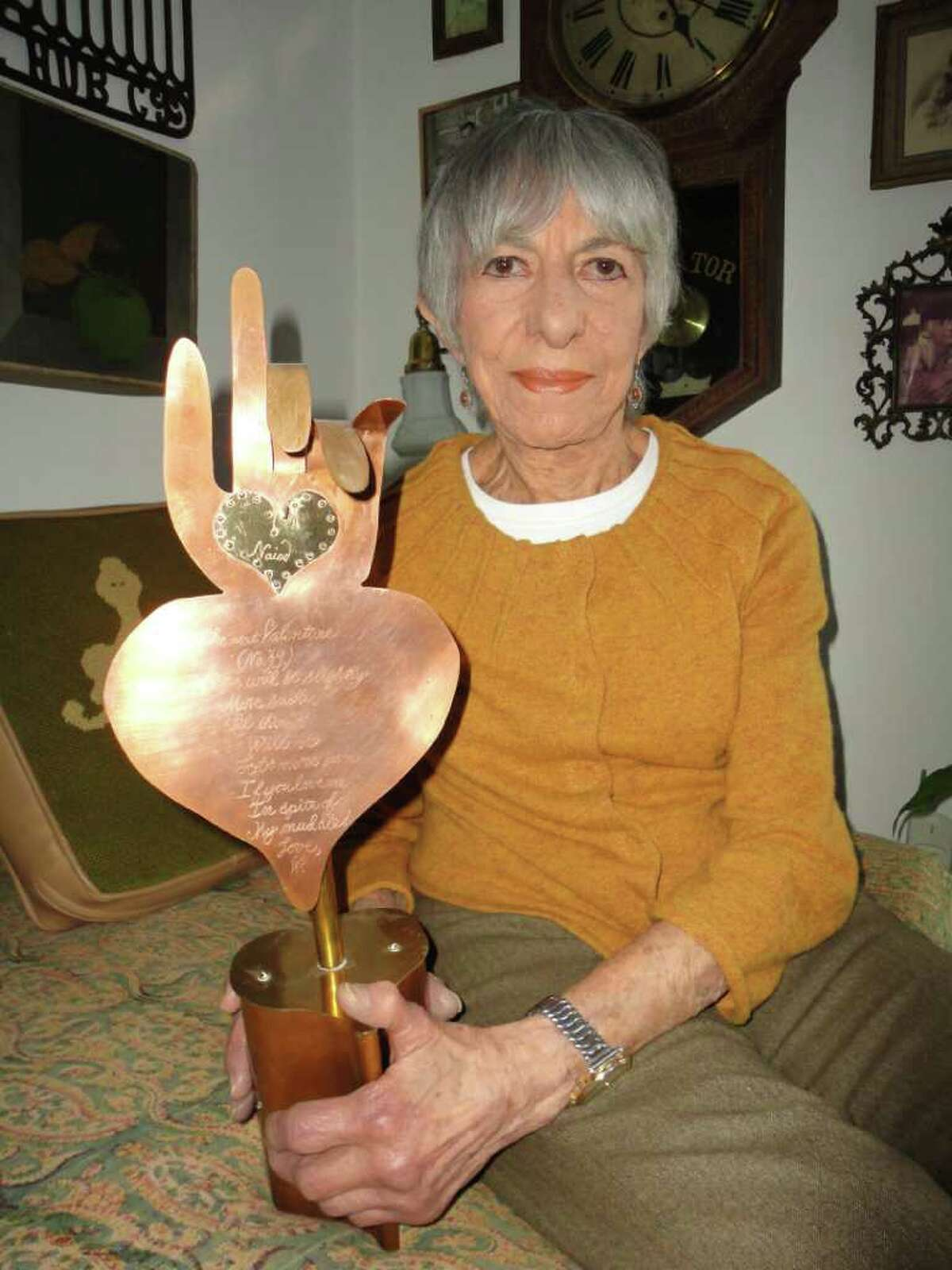 """Westport artist Naiad Einsel holds one of the metal sculptures her husband Walter made for her for Valentine's day after he had suffered a stroke. It asks her to love him """"in spite of my muddle."""""""