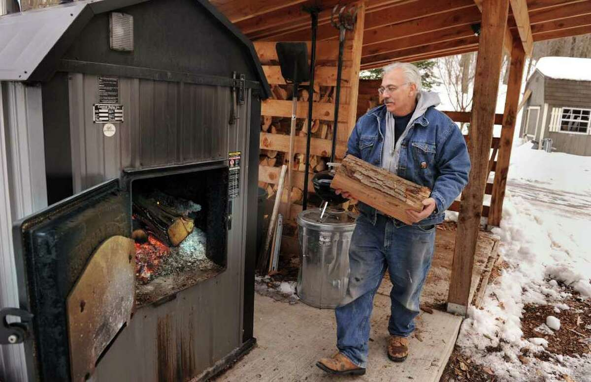 Frank Dascano, 65, of Danbury feeds logs into his outdoor furnace. He does this once in the morning and again in the evening. He usually uses five or six logs each time.