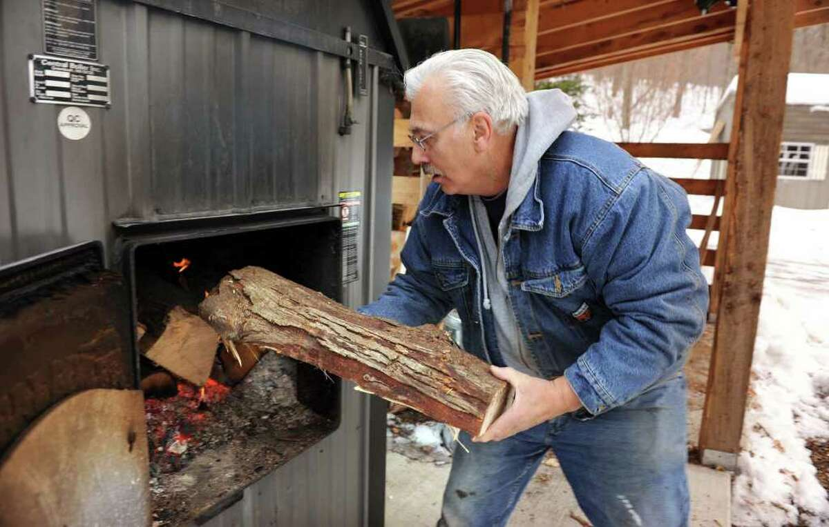 Frank Dascano, 65, of Danbury feeds logs into his outdoor furnace. He does this once in the morning and again in the evening. Usually he uses five or six logs each time.