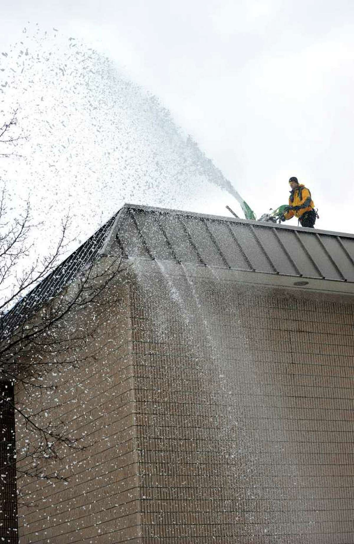 Joe Quaranta of Roxbury uses a snowblower on the roof of Schaghticoke Middle School in New Milford Tuesday, February 8, 2011.