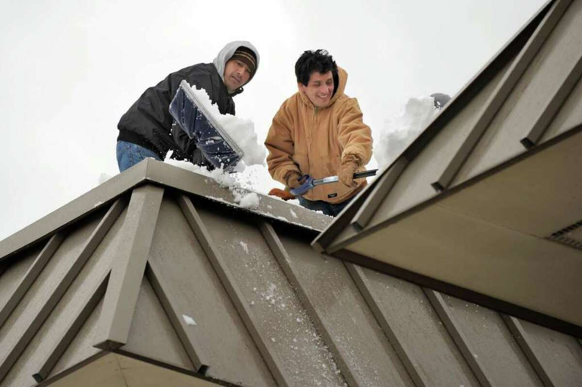 Men with shovels work to clear snow off the roof at Schaghticoke Middle School in New Milford Tuesday, February 8, 2011.