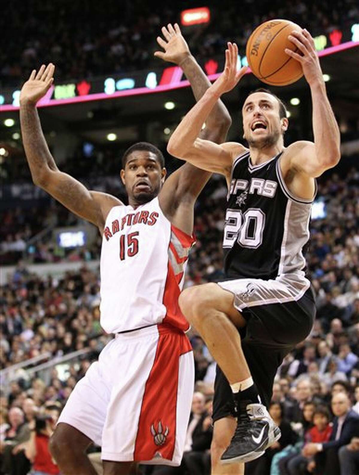The Spurs' Manu Ginobili drives in against the Raptors' Amir Johnson on Wednesday in Toronto.