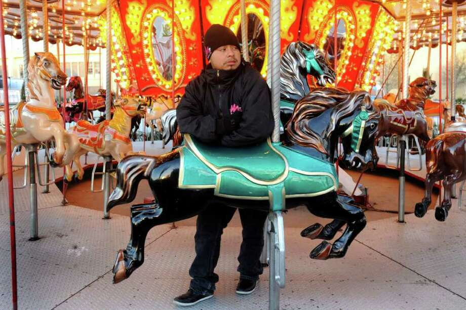 Antonio de Jesus, who operates a merry-go-round during the San Antonio Stock Show & Rodeo, waits for customers on the fairgrounds at the AT&T Center on a cold Wednesday, Feb. 9, 2011. Photo: BILLY CALZADA, SAN ANTONIO EXPRESS-NEWS / gcalzada@express-news.net