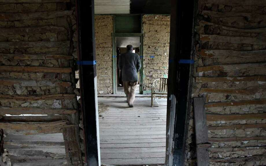 Ron Bauml, property restoration manager for the San Antonio Conservation Society, walks through a structure built around the 1840s on the Blas Herrera Ranch south of the city. Photo: JOHN DAVENPORT, SAN ANTONIO EXPRESS-NEWS / jdavenport@express-news.net