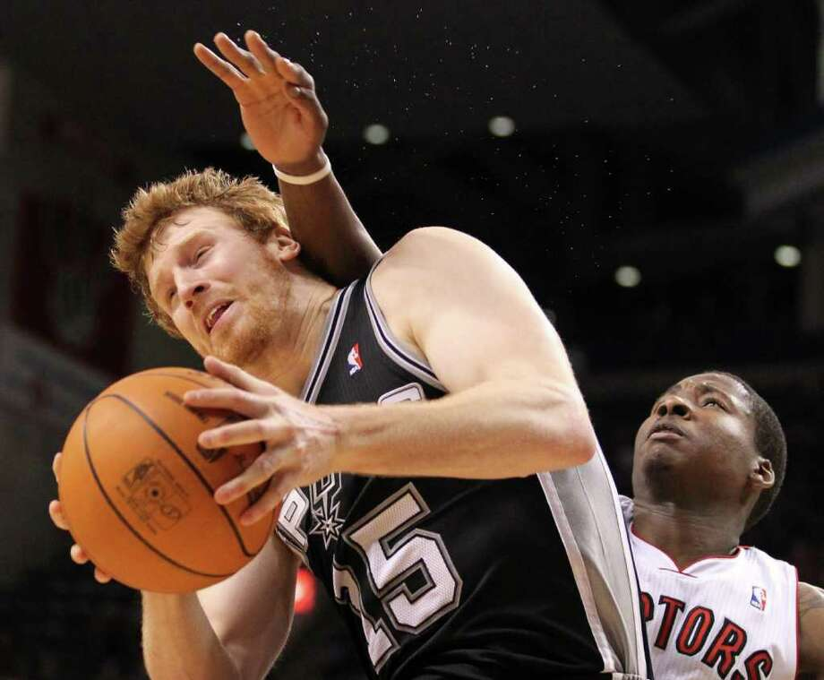 Toronto Raptors forward Ed Davis, rear, fouls San Antonio Spurs forward Matt Bonner during the second half of an NBA basketball game in Toronto on Wednesday, Feb. 9, 2011. Photo: AP