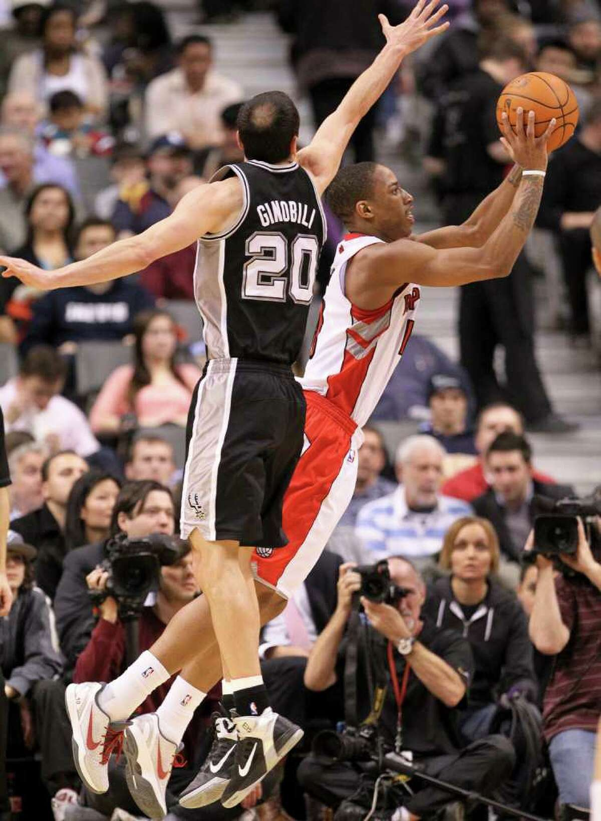Toronto Raptors guard DeMar DeRozan, right, shoots past San Antonio Spurs guard Manu Ginobili during the first half of an NBA basketball game in Toronto on Wednesday, Feb. 9, 2011.