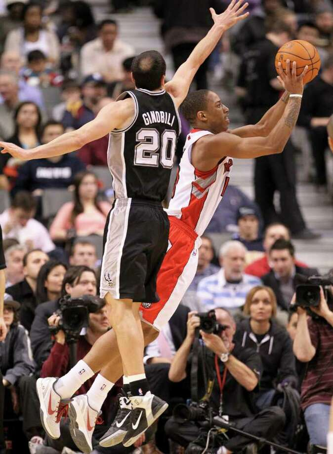 Toronto Raptors guard DeMar DeRozan, right, shoots past San Antonio Spurs guard Manu Ginobili during the first half of an NBA basketball game in Toronto on Wednesday, Feb. 9, 2011. Photo: AP