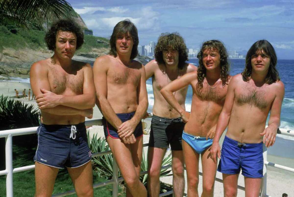 Hard rock group AC/DC at the beach in Ipanema, Brazil during a South American tour, January 1985. Left to right: Brian Johnson, Cliff Williams, Simon Wright, Angus Young, Malcolm Young.