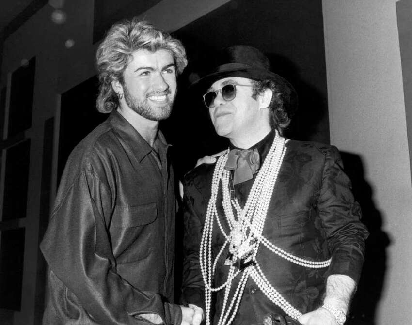 Pop star Elton John (right) congratulates George Michael on winning the Ivor Novello Songwriter of the Year Award at London's Grosvenor House Hotel, 13th March 1985.