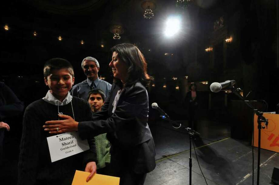 Mateen Sharif, a sixth-grader from Guilderland, is congratulated onstage Wednesday by his mother, Mary Derwesh, right,  his father, Farooq Shariff, second from left, and his brother Massoud, 10,  after winning the 2011 Capital Region Spelling Bee at Proctors in Schenectady. ( Philip Kamrass / Times Union ) Photo: PHILIP KAMRASS