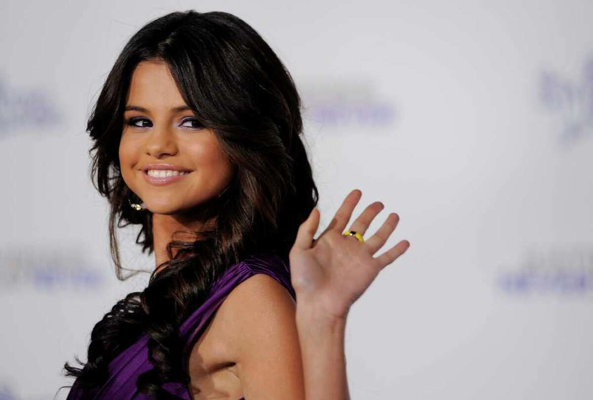 Selena Gomez waves to photographers at the premiere of the documentary film