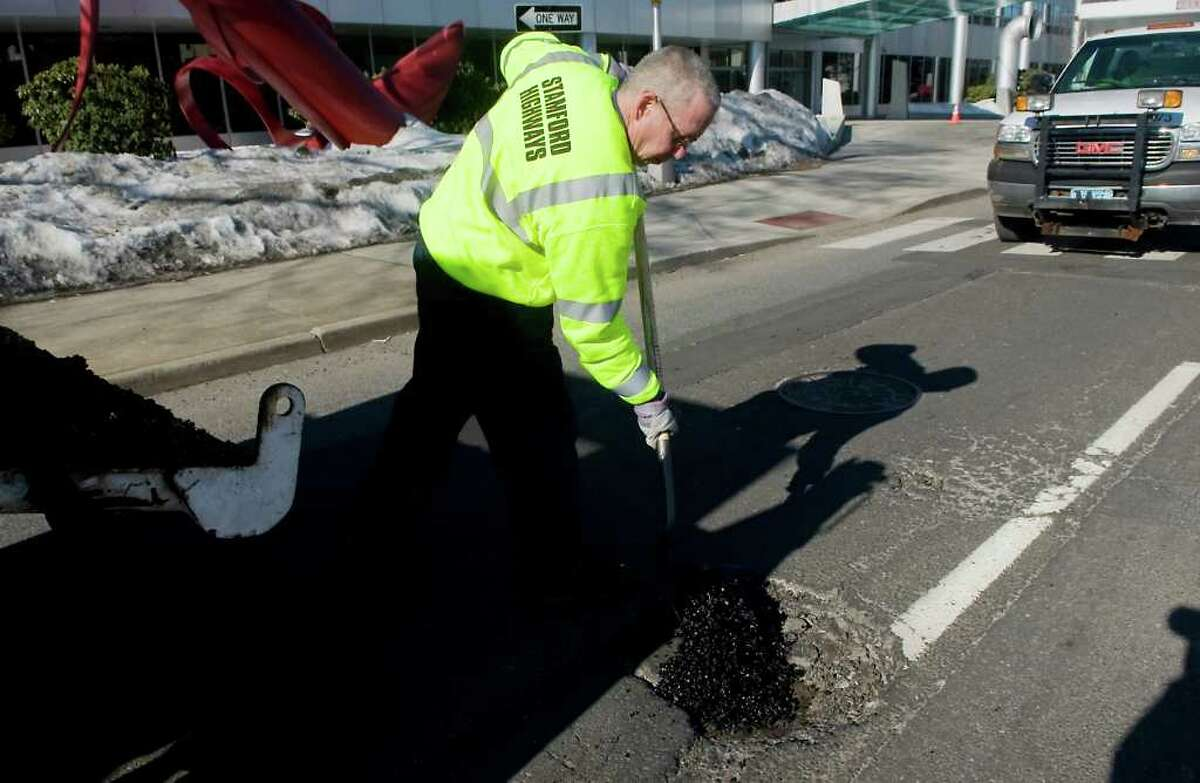 Robert Frattaroli, with the City of Stamford Highways and Road Maintenance department, fills potholes along Summer Street in Stamford, Conn. on Thursday February 10, 2011.