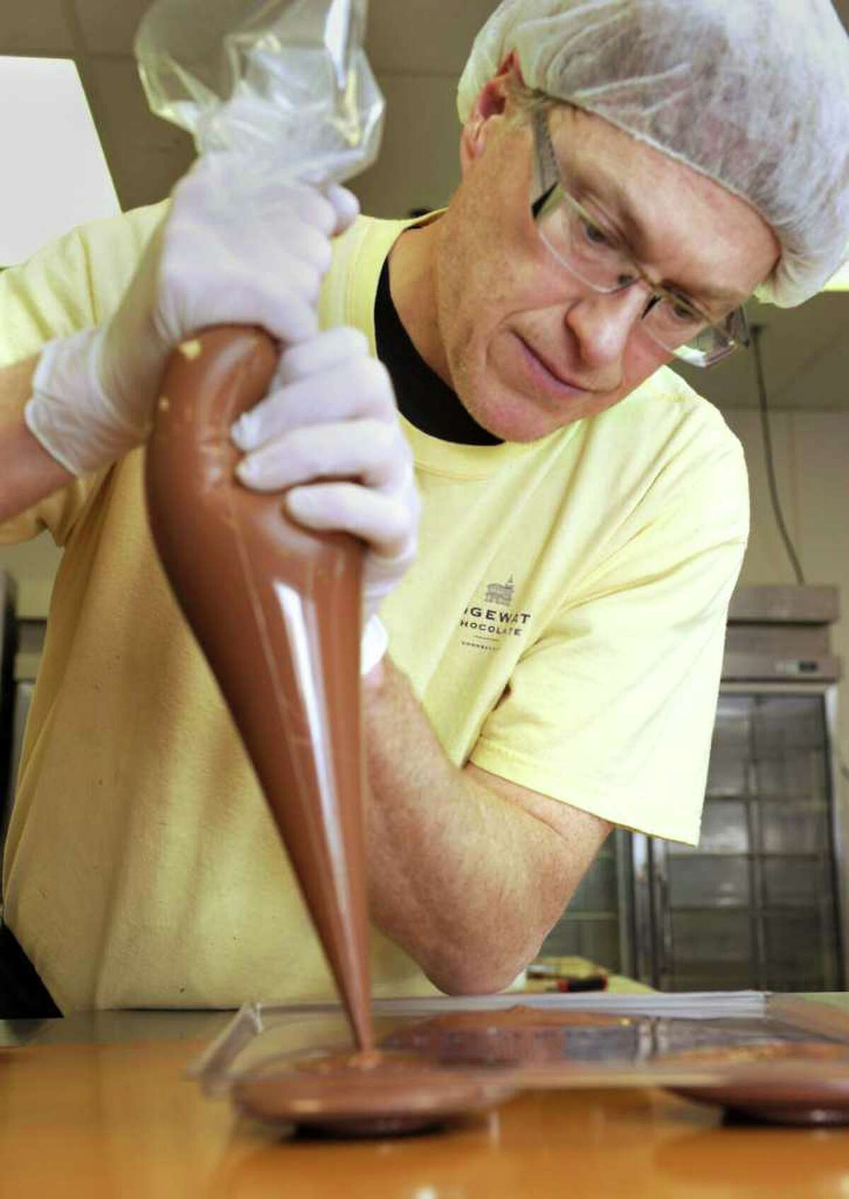 Erik Langegren, founder and co-owner of Bridgewater Chocolates, fills heart molds with chocolate Thursday, February 10, 2011