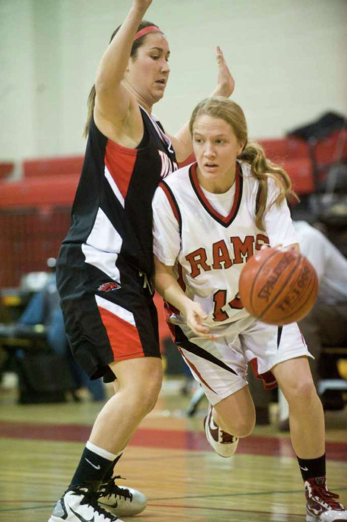New Canaan's Sarah Mannelly moves the ball past Warde's Taylor Bargmann as New Canaan hosts Fairfield Warde in a girls basketball game in New Canaan, Conn., February 10, 2011.