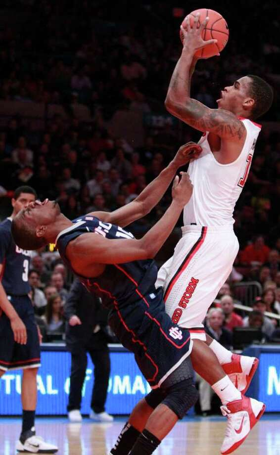 St. John's Dwight Hardy, right, scores as he is fouled by Connecticut's Kemba Walker in the second half of an NCAA college basketball game Thursday, Feb. 10, 2011, in New York. Hardy scored 33 points as St. John's won the game 89-72. (AP Photo/Frank Franklin II) Photo: AP