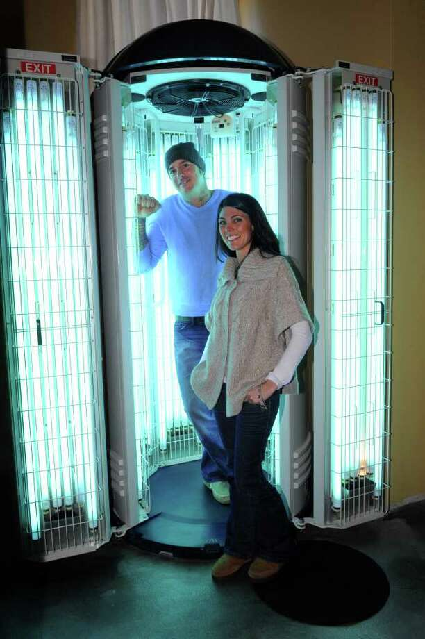 Anthony Lukac and Nichole Wells, co-owners of Miami Sun Factory in Stratford, pose for a photo with a stand-up tanning bed in their new location at 2362 Main Street on Thursday, Feburary 3, 2011. Photo: Lindsay Niegelberg / Connecticut Post
