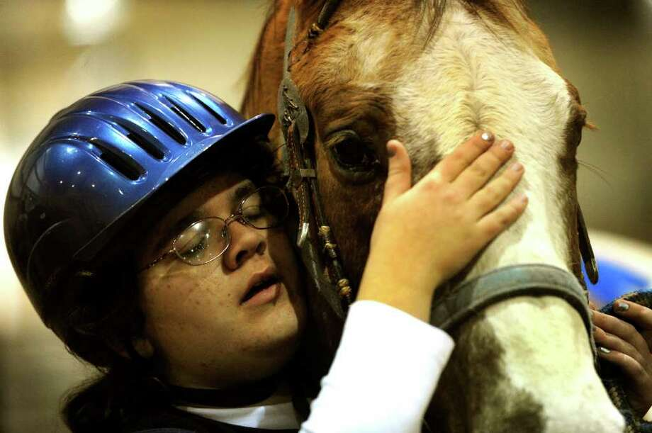 Louise Perdue, 14, who has been riding for four years, embraces a horse before riding during an Thursday, Feb. 10, 2011, exhibition on the grounds of the San Antonio Stock Show & Rodeo by Riding Opportunities Promoting Exceptional Riders. ROPER is a group for people with disabilities. Photo: BILLY CALZADA, SAN ANTONIO EXPRESS-NEWS / gcalzada@express-news.net