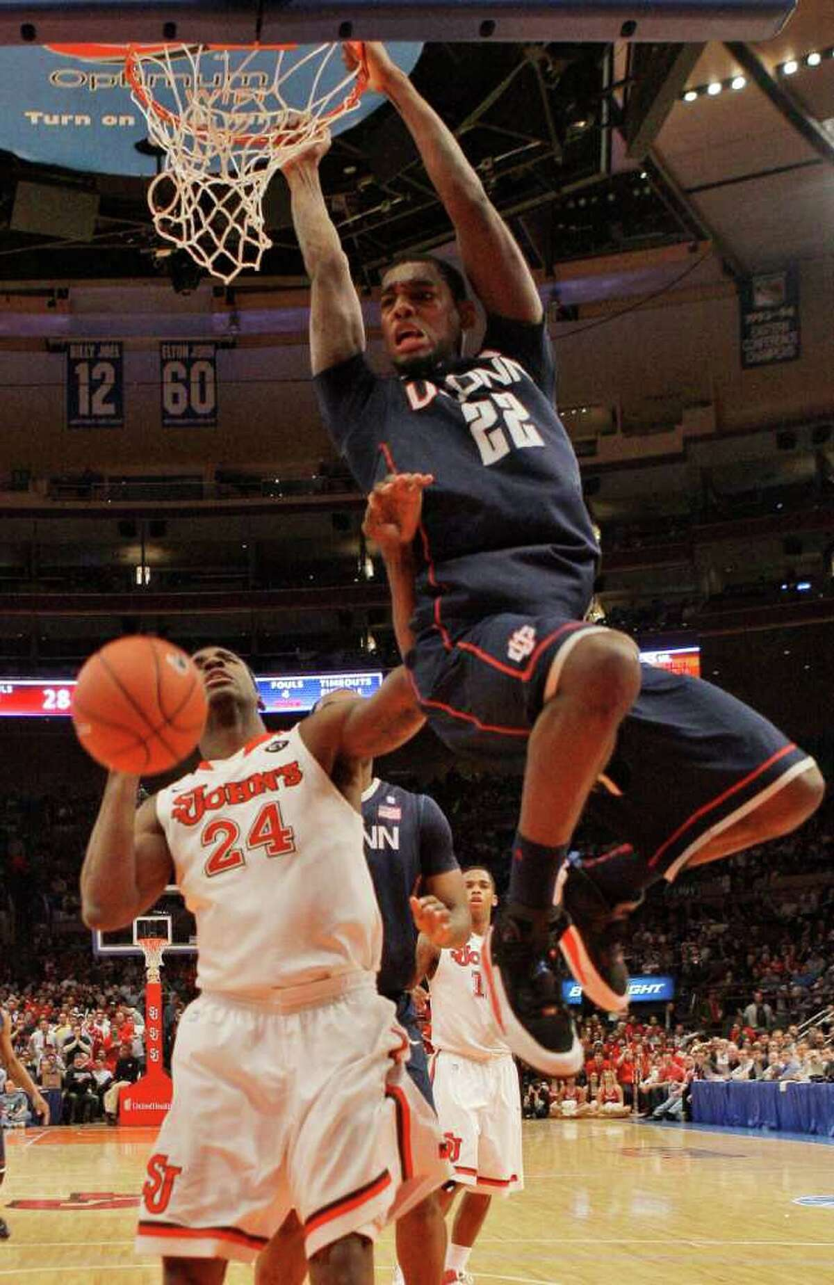 Connecticut's Roscoe Smith (22) dunks the ball over St. John's Justin Burrell (24) in the first half of an NCAA college basketball game Thursday, Feb. 10, 2011, in New York. (AP Photo/Frank Franklin II)