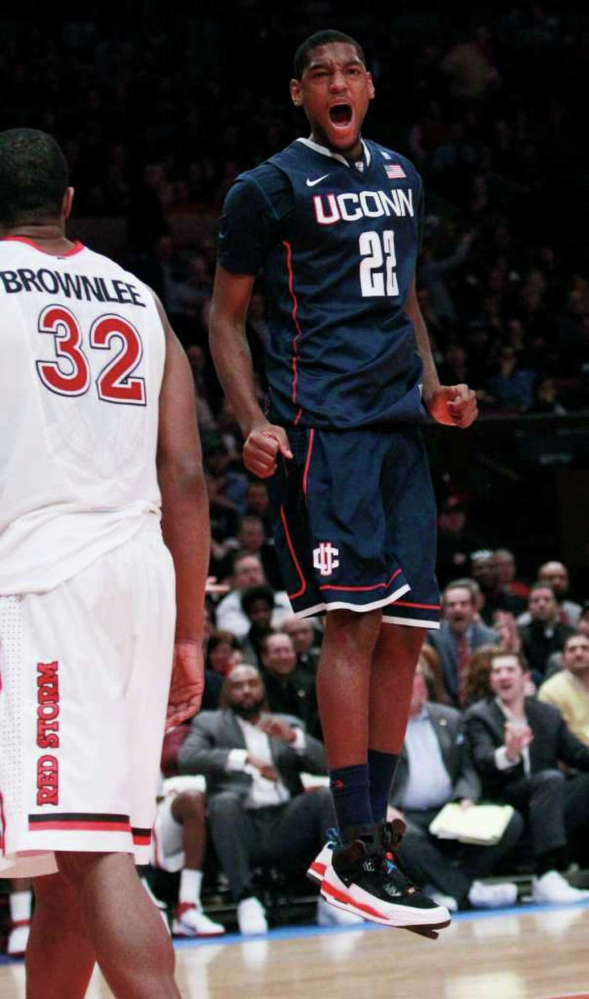 Connecticut's Roscoe Smith (22) reacts after dunking the ball as St. John's Justin Brownlee (32) walks away in the first half of an NCAA college basketball game Thursday, Feb. 10, 2011, in New York. (AP Photo/Frank Franklin II)