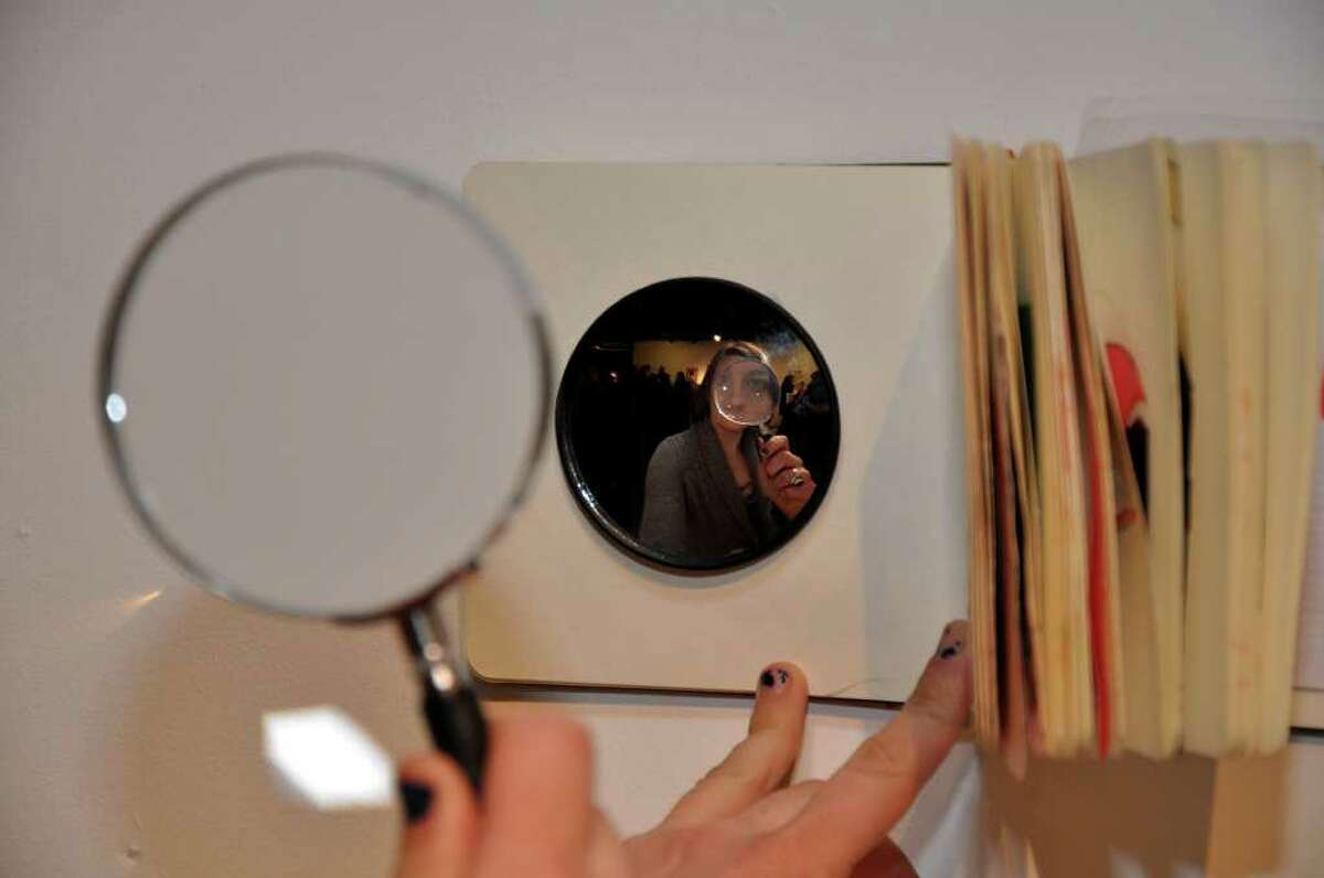 """Amy Bilden, of Norwalk, looks through a magnifying glass to view her mixed media work titled """"Closer Look"""" during the Factory Underground art gallery's opening on Saturday, Feb. 5, 2011."""