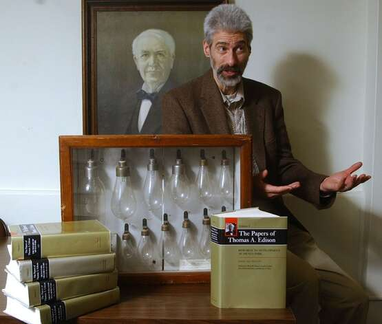 "Historian Paul Israel, director of the Thomas A. Edison Papers project at Rutgers University, talks about the publication of the fifth volume of ""The Papers of Thomas A. Edison,"" at his office at Rutgers in Piscataway, N.J., Thursday, Oct. 21, 2004. The publication of Volume Five of a projected 15 volumes of Edison's papers coincides with Edison's first successful experiment on the incandescent lamp at the Menlo Park laboratory in Edison, N.J., according to Rutgers. Israel sits next to a display of early electric lamps from Edison's lab. (AP Photo/Mike Derer)"