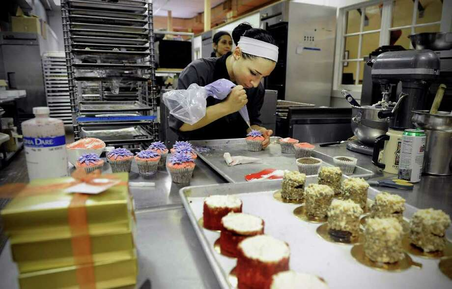 Pastry chef Lauren DiSessa prepares chocolate cupcakes with vanilla butter cream frosting at Chocopologie Cafe in Norwalk, Conn. on Friday February 11, 2011. Photo: Kathleen O'Rourke / Stamford Advocate