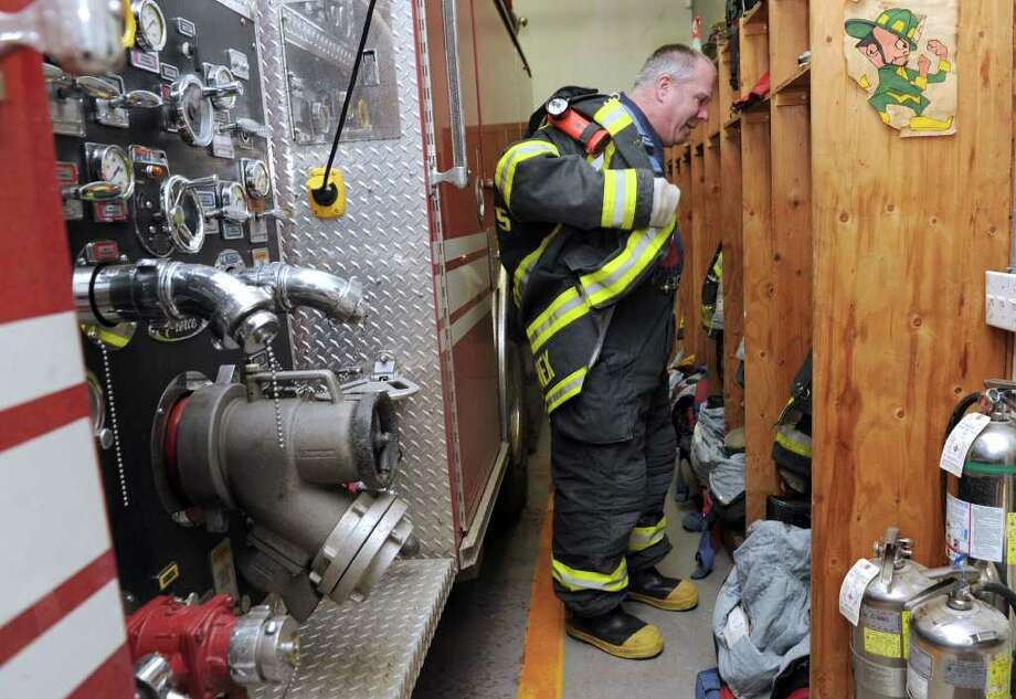 Charlie Zilinek, a volunteer with Wooster Hose Company #5, on Coalpit Road in Danbury, shows how tight the room  is between the fire truck and the lockers where the firefighters gear up to before heading to a fire call. Photo: Carol Kaliff / The News-Times