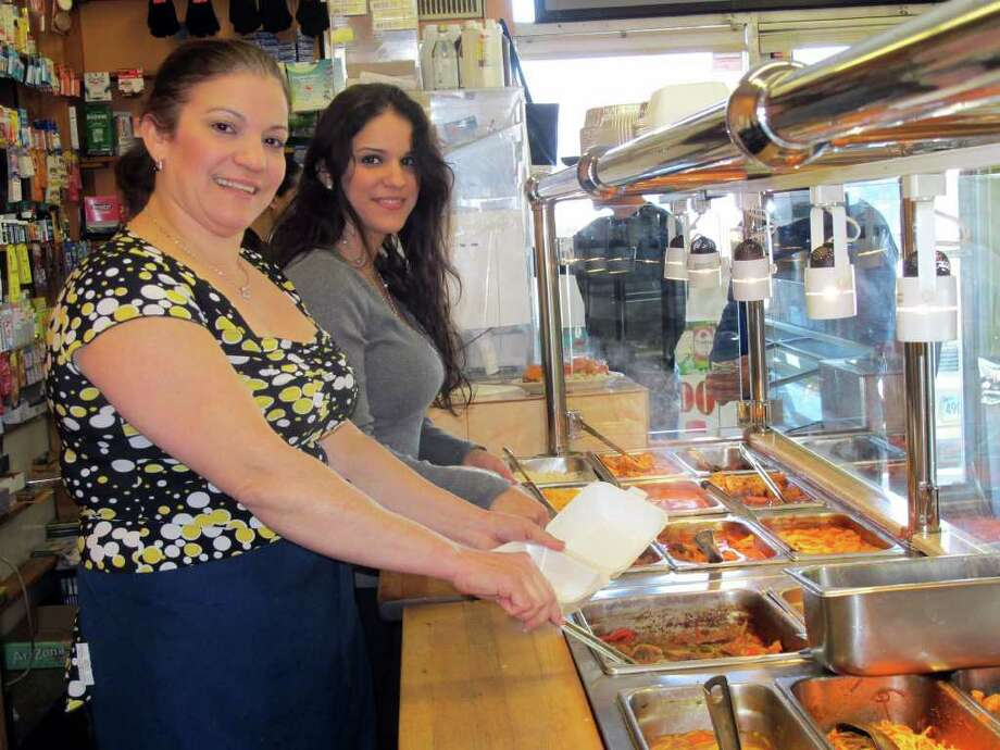 Luisa Nunez, left, and her daughter Alba Nunez, right, work at Espinal Grocery and Deli at 28 North Street and like having Padanarum Hose Co. #3 across the street. Photo: Stacy Davis / The News-Times