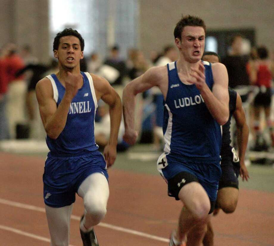 Bunnell's Jordan Dudley, left, and Fairfield Ludlowe's Tyler Schwarz compete in a heat of the 55 meter dash, during Class L track championship action in New Haven, Conn. on Friday February 11, 2011. Photo: Christian Abraham / Connecticut Post